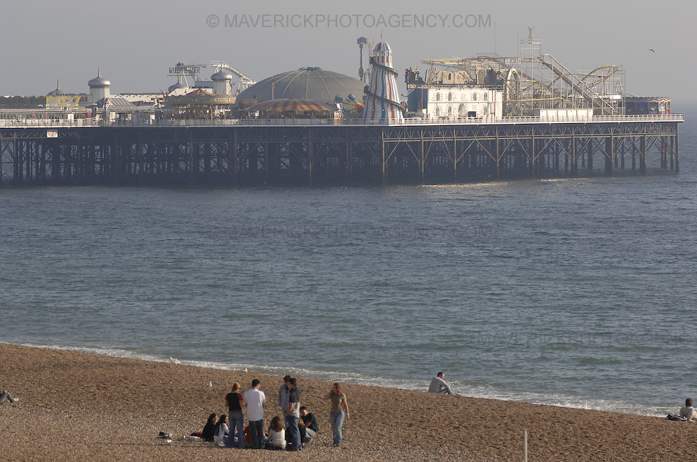 People walk on Brighton beach in southern England with the famous Brighton Pier in view.
