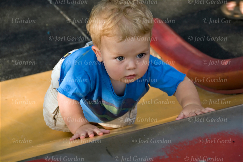 1 year old toddler boy crawling on hands and knees exploring his environment in outdoor playground