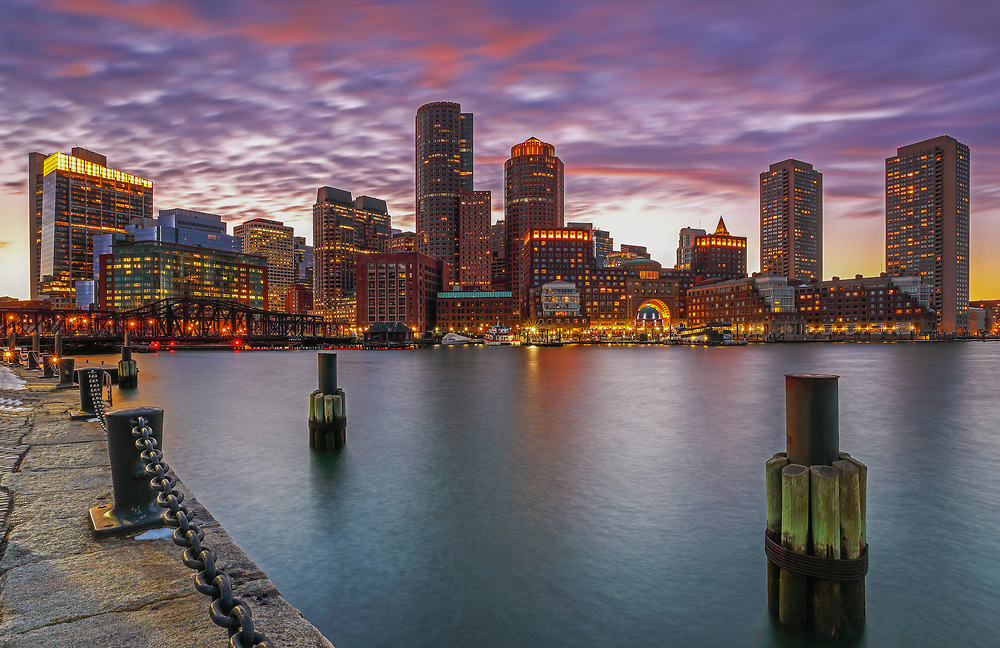 Boston Harbor skyline photography from New England Photography Guild member and award winning fine art photographer Juergen Roth showing Boston Financial Waterfront District landmarks such as One International Place, Boston Harbor Hotel, Independence Wharf, Department of Homeland Security building, and other structures along Rowes Wharf photographed on a beautiful winter sunset evening. The last light was painting the cloudscape in fire red hues and the long exposure time ensured the intentional blurry cloud movement. <br />