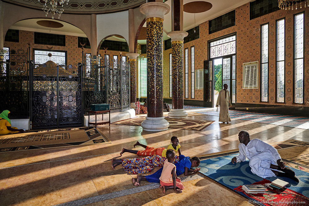 A clergyman teaches children the Quran at the mausoleum of Sokhna Mame Diarra Bousso, the mother of Amadou Bamba. Sokhna Mame Diarra Bousso (1833-1866) is worshipped as a saint. The annual pilgrimage to her mausoleum is the only pilgrimage dedicated to a woman in Senegal.