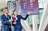 Mature businessman showing his boarding pass with the attractive airport staff
