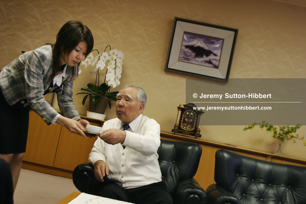 An assistant removes an empty tea cup from Osamu Suzuki, Chairman and CEO of Suzuki Motor Corporation, in the company boardroom, in Hamamatsu, Japan, on Tuesday, Apr. 25th 2006. During interviews it is common for female assistants to enter the rooms silently , bringing refreshment drinks of green tea, coffee, or orange juice, to the company head and his guests.
