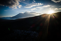 Aerial drone image of Volcán de Fuego and Volcán de Acatenango (left and right peaks in the distance) at sunset, seen from above Antigua Guatemala, on Tuesday, August 21, 2018. While Acatenango is dormant, Fuego is highly active and an eruption on June 3, 2018 caused heavy loss of life and property.