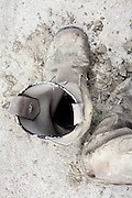 overhead view of old leather boots with dried up mud