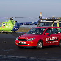 A unique 'Blue Light' assembly to place today at Perth Airport (12.02.15), home of Scotland's Charity Air Ambulance. SCAA will soon mark it's 500th emergency callout and to commemorate this landmark and to pay thanks to and acknowledge the working relationship with other vital services - crews, vehicles and aircraft who work alongside SCAA within the emergency 999 response network in Scotland gathered for this photograph. The line-up including police, ambulance, fire & rescue, coastguard, moutain rescue teams, RNLI, BASICS Scotland, First Responders and Royal Navy Search & Rescue. Pictured shows Helimed 76 with Trossachs Search and Rescue<br /> Picture by Graeme Hart.<br /> Copyright Perthshire Picture Agency<br /> Tel: 01738 623350  Mobile: 07990 594431