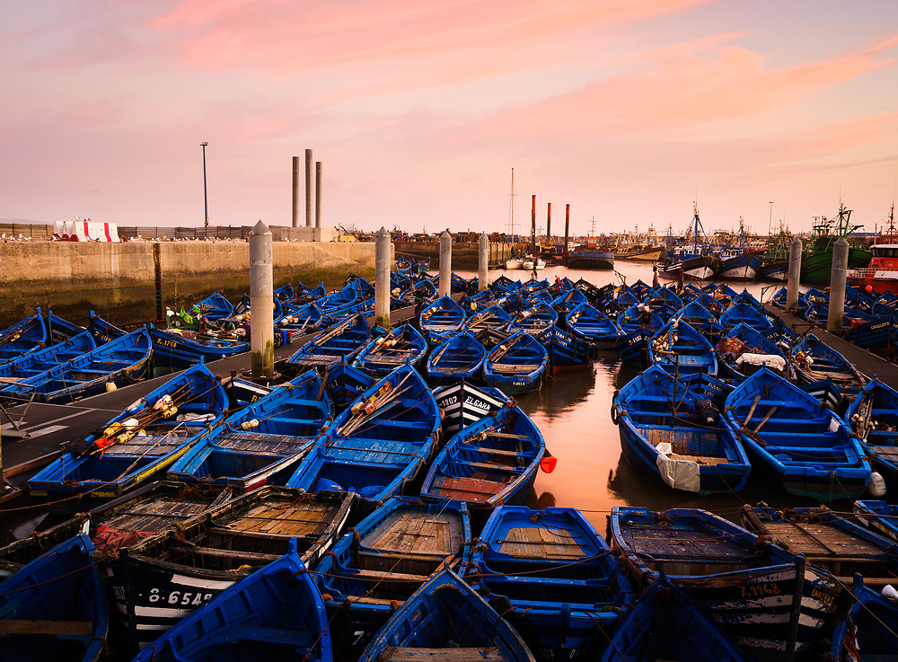 ESSAOUIRA, MOROCCO - CIRCA MAY 2018:  Fishing boats over the port of Essaouria at sunset.