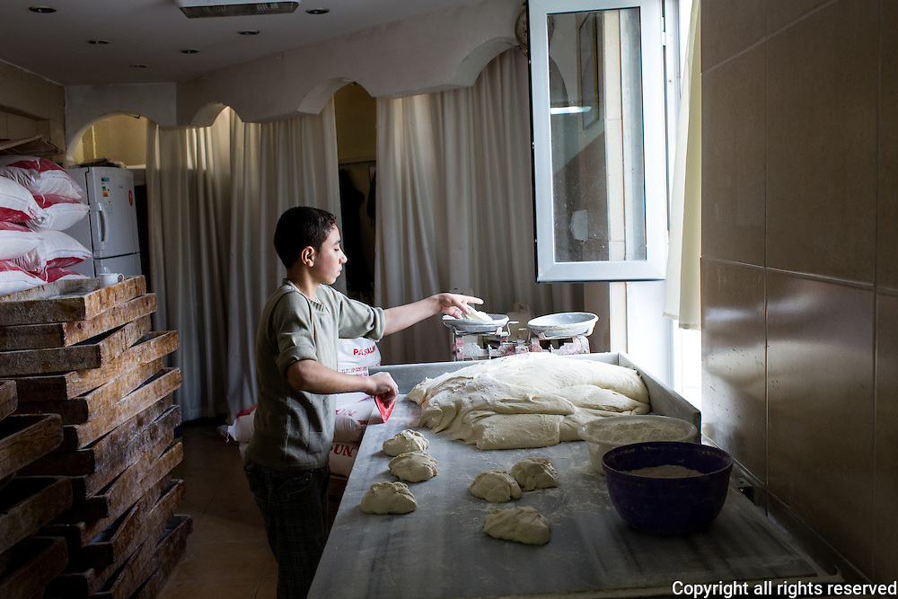 A young baker's apprentice measures out dough for pide. Antakya, Turkey