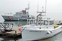 A Coast Guard cutter slips past a lobster boat tied up at the Town Pier on a foggy day in Bar Harbor, Maine