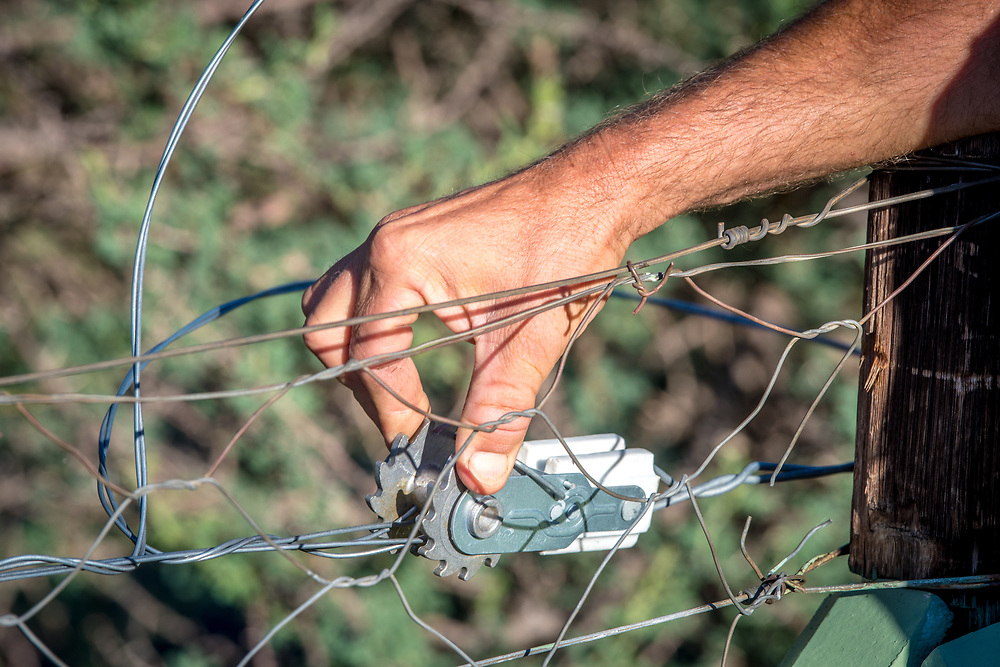 Farmer checking electric fence wire stretcher on fencing at Dabis Guest Farm in Helmeringhausen, southern Namibia, Africa.