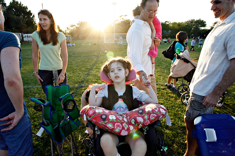 MELISSA LYTTLE   |   Times<br /> SP_351237_LYTT_TWINS_2 (March 16, 2012, Clearwater, Fla.) While Olivia Scheinman, 7, and her parents sat on the sidelines cheering Hailey  on during her soccer game, a family approached and complimented Olivia's wheelchair saying their daughter Olivia had the same one. The moms Allison Scheinman and Erica Reger, left, bonded over both having daughter's with disabilities named Olivia, while the dad's Jon Scheinman and Craig Reger bonded over having daughters playing soccer. The Regers recently moved to the area from New York, and their daughter Cassandra, 8, just joined Hailey's soccer team. The families shared their thoughts about therapy, schools and neighborhoods and exchanged phone numbers to keep in touch. Holding his daughter Olivia, 7, in his arms, Craig Reger takes Olivia Scheinman's hand in his and tells her how nice it was to meet her, before the families parted ways for the evening.  [MELISSA LYTTLE, Times]