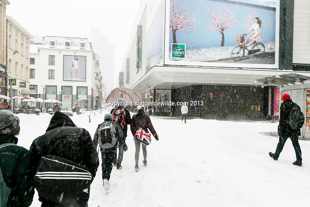 Brussel 12 maart 2013. Zware sneeuwbuien teisteren geheel Belgie. De langste files sinds tijden. Het verkeer, bussen, treinen hebben veel last van de sneeuw.In het centrum van de stad Brussel (Nieuwstraat) hangen  vrolijk gekleurde reclameborden met bloesem en fietsplezier. Op straat was iets minder zonnig. De lente is ver te zoeken.Inno