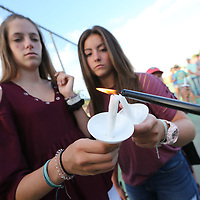 Molly Nichols, 14, left, and Jayla Harris, 14, get their candles lite before Monday's vigil for Magiie Riley and Brandon Coward at Nettleton High School.