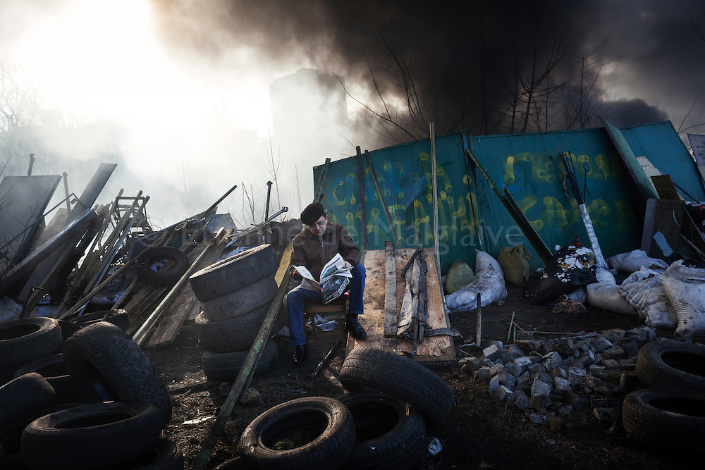Anti-government protesters on the watch at a barricade on Instituska street near Maidan Square where deadly clashes occured with police shooting at protesters the previous day,  February 21, 2014 in Kiev, Ukraine.
