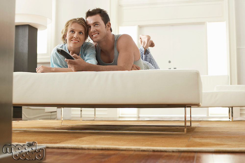 Couple on bed watching television together man holding remote control