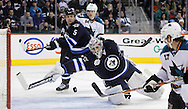 Image not for sale. Winnipeg Jets' goaltender Ondrej Pavelec (31) makes a miraculous paddle save against the San Jose Sharks' early in the third period of NHL action at MTS Centre, January 12, 2011. Winnipeg Jets' Mark Stuart (5) and San Jose Sharks' Jamie McGinn (64) look on behind him.