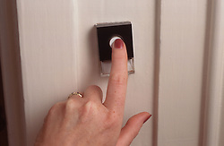Finger pressing doorbell,