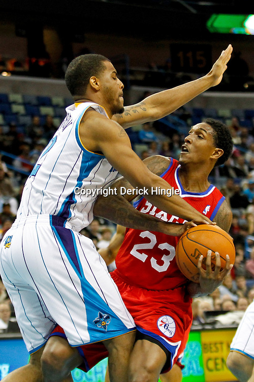 January 4, 2012; New Orleans, LA, USA; Philadelphia 76ers point guard Lou Williams (23) is defended by New Orleans Hornets shooting guard Trey Johnson (12) during the second half of a game at the New Orleans Arena. The 76ers defeated the Hornets 101-93.  Mandatory Credit: Derick E. Hingle-US PRESSWIRE