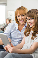 Happy mother and daughter using tablet PC with family sitting in background at home