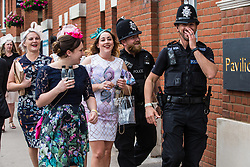 Ascot, UK. 20 June, 2019. Racegoers share a joke with police officers as they leave Royal Ascot after attending Ladies Day.