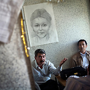 Government opposition members (facing camera) in the southern Russian republic of Kalmykia discuss politics with a visitor in the capital Elista. ..Above them hangs a picture of Larisa Yudina, editor of the republic's only opposition newspaper. She was stabbed repeated and left to die in a pond in 1998. ..Yudina was one of the harshest critics of the republic?s president, Kirsan Ilyumzhinov, who strenuously rejected allegations of involvement in her murder. ..Ilyumzhinov, 44, who is also the president of the World Chess Federation, Fide, is hosting one of the world?s most important matches in history. ..The match beginning September 21 in Elista, the capital of Europe?s only Buddhist nation, will end a 13-year split in the game that has produced rival claims to the title. ..Veselin Topalov, a Bulgarian ranked first according to Fide, will play against Vladimir Kramnik, who is the Classical Chess World Champion, a title established after Garry Kasparov led a breakaway from Fide in 1993. The two grandmasters, both aged 31, will face each other for the right to be undisputed world chess champion...A Buddhist millionaire businessman, Ilyumzhinov acquired his wealth in the economic free-for-all which followed the collapse of the Soviet Union. ..At the age of just over 30, he was elected president in 1993 after promising voters $100 each and a mobile phone for every shepherd. Soon after, he introduced presidential rule, concentrating power in his own hands. ..He denies persistent accusations of corruption, human rights abuses and the suppression of media freedom. When Mr Ilyumzhinov has been president of the International Chess Federation (FIDE) since 1995 and has been enthusiastic about attracting international tournaments to Kalmykia. His extravagant Chess City has led to protests by its impoverished citizens..