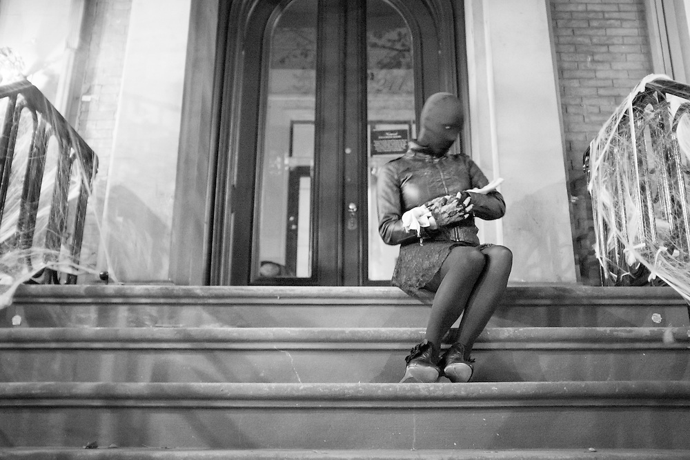 Black and white of a masked woman cradling a fake hand, holding it like a baby, in New York City, USA