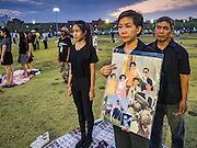 17 OCTOBER 2016 - BANGKOK, THAILAND: People stand at attention during the playing of the Thai National Anthem on Sanam Luang. Millions of Thais are mourning the passing Thai King Bhumibol Adulyadej who died Oct. 13, 2016. He was 88. His death comes after a period of failing health. Bhumibol Adulyadej, was born in Cambridge, MA, on 5 December 1927. He was the ninth monarch of Thailand from the Chakri Dynasty and is also known as Rama IX. He became King on June 9, 1946 and served as King of Thailand for 70 years, 126 days. He was, at the time of his death, the world's longest-serving head of state and the longest-reigning monarch in Thai history.        PHOTO BY JACK KURTZ