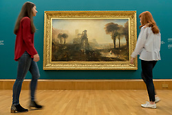 "© Licensed to London News Pictures. 25/05/2018. LONDON, UK. Staff members view ""Caligula's Palace and Bridge"", 1831, by J.M.W. Turner at the preview of Fire and Water, a display of masterpieces by Constable and Turner at Tate Britain.  On display for the first time in 180 years alongside each other are ""Salisbury Cathedral from the Meadow"", 1831, by John Constable and ""Caligula's Palace and Bridge"", 1831, by J.M.W. Turner.  The works will on display 26 May 208 to July 2019.  Photo credit: Stephen Chung/LNP"