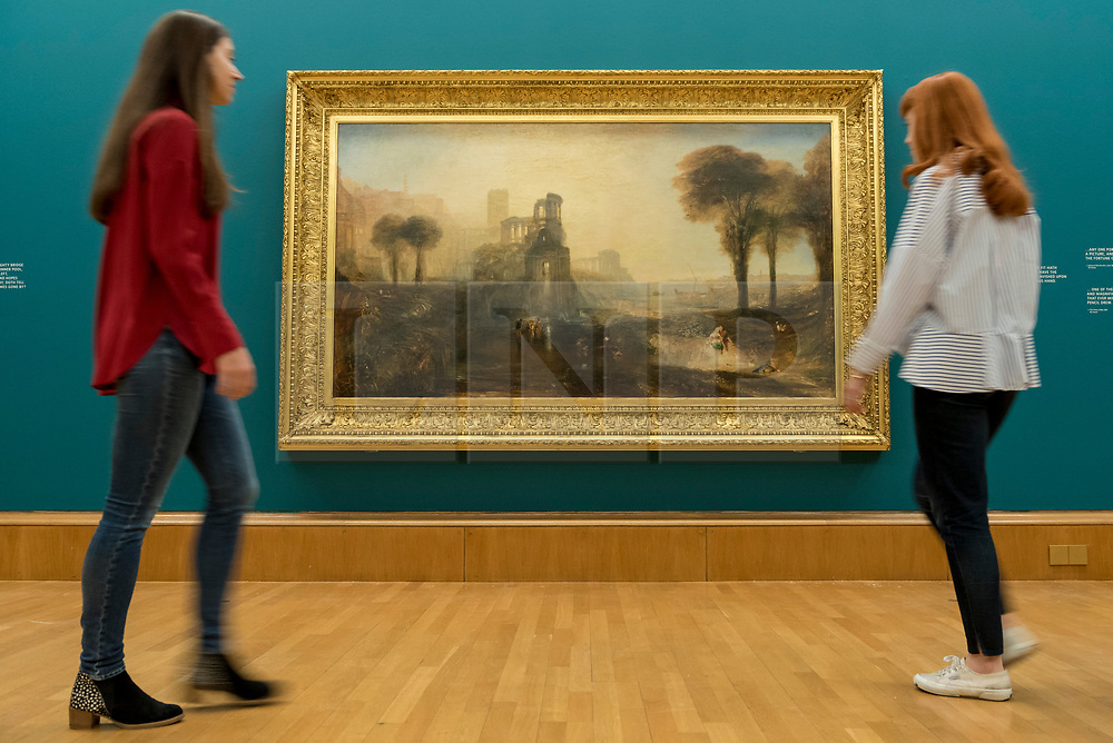 """© Licensed to London News Pictures. 25/05/2018. LONDON, UK. Staff members view """"Caligula's Palace and Bridge"""", 1831, by J.M.W. Turner at the preview of Fire and Water, a display of masterpieces by Constable and Turner at Tate Britain.  On display for the first time in 180 years alongside each other are """"Salisbury Cathedral from the Meadow"""", 1831, by John Constable and """"Caligula's Palace and Bridge"""", 1831, by J.M.W. Turner.  The works will on display 26 May 208 to July 2019.  Photo credit: Stephen Chung/LNP"""