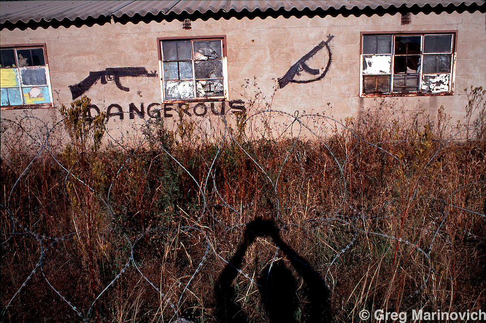 POLITICS TOKOZA SOUTH AFRICA 1995: Graffiti warns of the dangers in side an Inkatha Freedom Party controlled workers hostel in a no-go zone in Tokoza township, South Africa, winter 1995. Part of The Dead Zone series. (Photo by Greg Marinovich / Getty Images)
