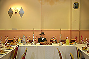 A 13 year-old Orthodox Jewish boy sits waiting for his Bar Mitzvah to begin in a Parces hall, Stamford Hill. The Bar Mitzvah signals the coming of age for a young Jewish boy, they become responsible to observe the commandments of the Torah. It coincides with physical puberty and they begin to participate in all areas of Jewish life. A Bar mitzvah ceremony is a big occasion, the young boy reads a section from the Torah to his family and friends and a mitzvah meal is consumed.