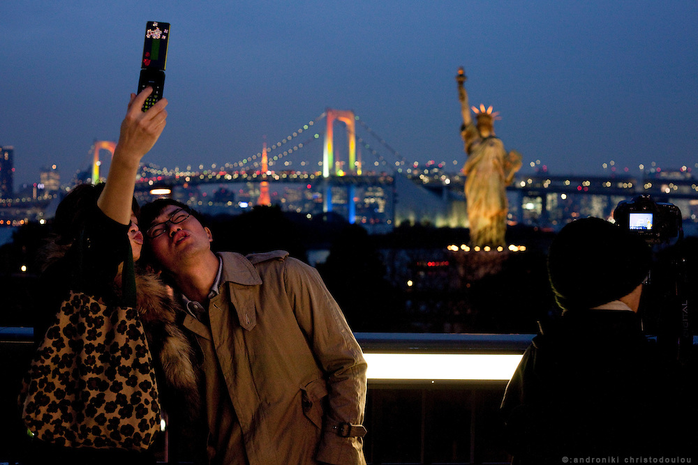 Japanese couple taking photos in front of Aqua City shopping mall in Odaiiba. The location offers one of the best night views of Tokyo cityscape.