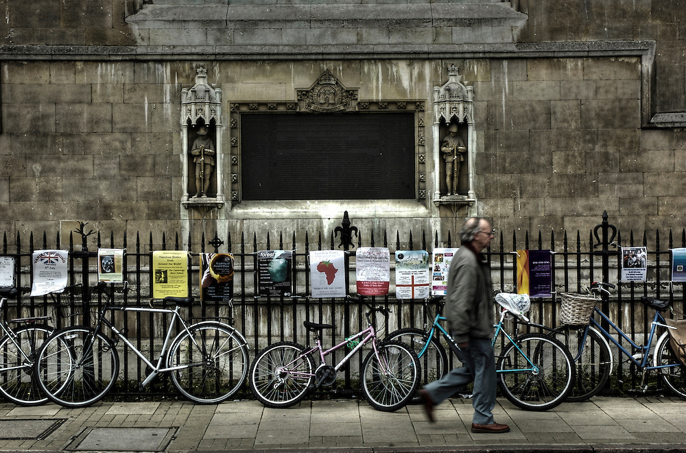 A middle aged man walking along a street in Cambridge, England past a line of bicycles