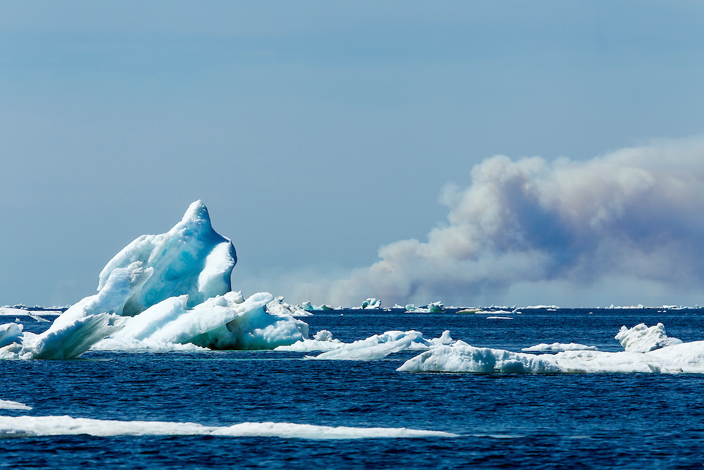 Canada, Manitoba, Melting sea ice and smoking forest fires near Cape Tatnum on Hudson Bay on warm summer morning