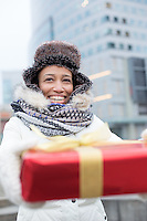 Happy woman holding gift during winter in city