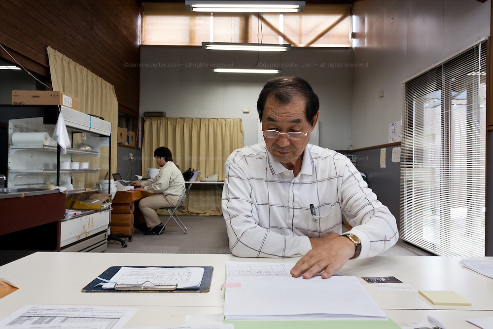 Isao Sanno (front) and Shuhei Suzuki (behind) working at the Becquerel Centre in a farmers' market in Miharu, where they test locally grown food for nuclear contamination. Miharu, Fukushima, Japan. Friday May 4th 2012
