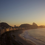 Praia de Copacabana at sunrise. Copacabana beach, one of the world's most famous urban beaches at sunrise with Sugar Loaf Mountain in the distance. The beach and hotel strip stretches for 1.5 miles (4km) from the Morro do Leme at the Northern end, to Arpoador. Copacabana beach, Rio de Janeiro,  Brazil. 21st July 2010. Photo Tim Clayton..