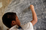 A student expresses his artistic talent on the blackboard after a day of classes at The Ban Buamlao Primary School in Ban Buamlao, Laos. The school has exhausted its paper supply, but many of the students enjoy this activity according to faculty members.