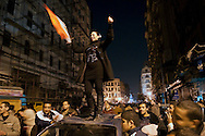 A woman holding an Egyptian flag dances atop a car on Talaat Harb Street in downtown Cairo, part of a massive street party celebrating the resignation of Hosni Mubarak, who ruled Egypt for 30 years. The car roof didn't fare so well. (Cairo, Egypt - February 11, 2011)