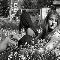 Girl friends sitting in long grass