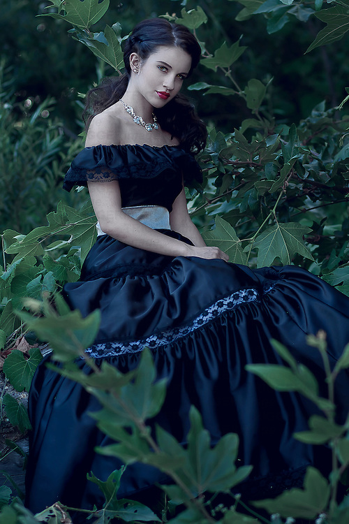 Glamorous young woman wearing off shoulder blue party dress sitting in garden