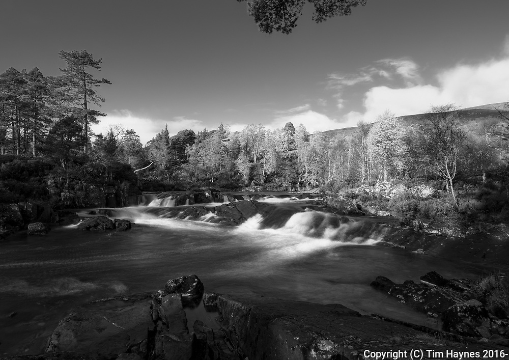 Beautiful strong autumn morning sunlight illuminating birch trees. <br /> Small cascades in the River Affric.