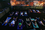 A nighttime yoga class held on a Manhattan rooftop.