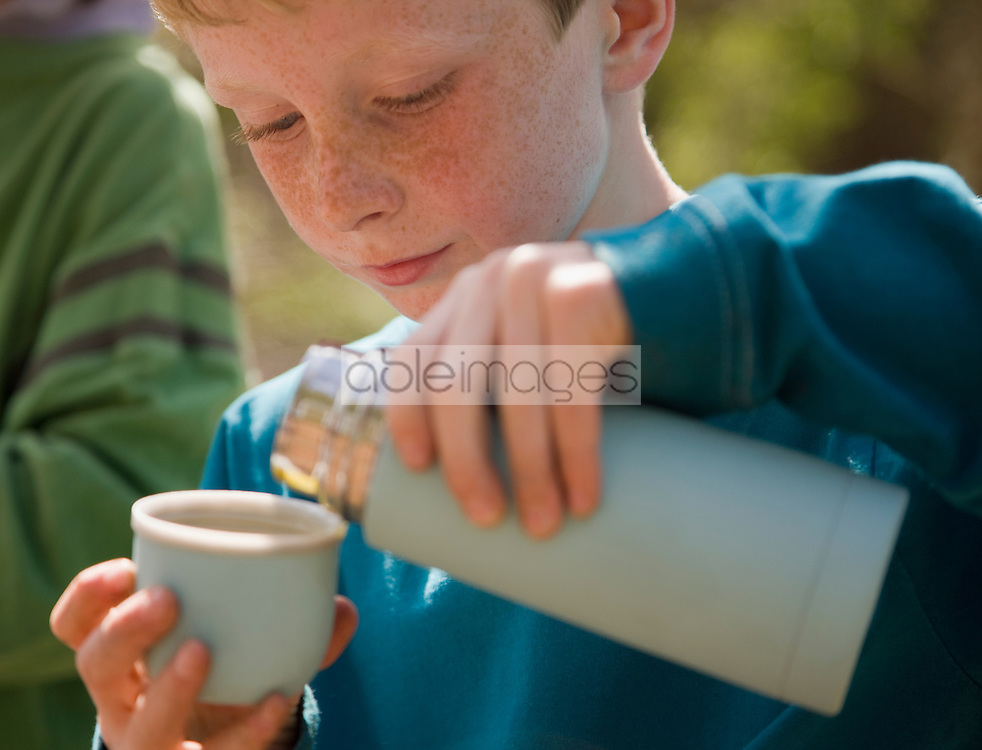 Close up of young boy pouring water from insulated flask