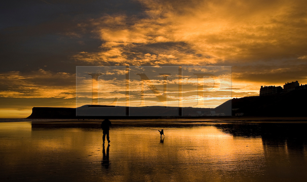 © Licensed to London News Pictures. 09/01/2012..Saltburn, England. ..A man walks his dog along the beach as a spectacular sunrise is seen over the Cleveland town of Saltburn by the Sea...Photo credit : Ian Forsyth/LNP