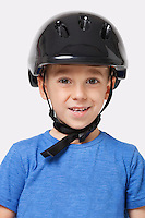 Portrait of a happy little boy wearing bicycle helmet over white background
