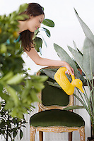 Woman watering plants with duck-shaped watering can