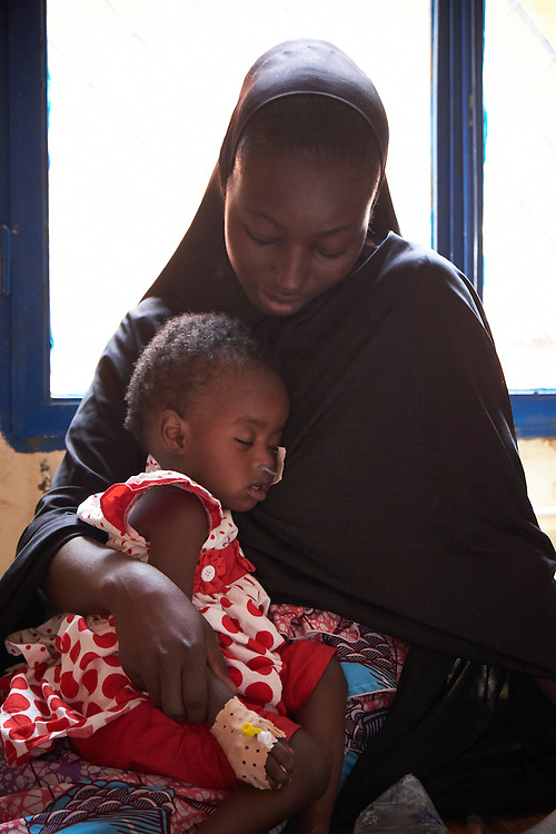 Halima Abdou, 22 years old with daughter Saratou, 18 months old at the centre for Treatment of Acute Malnutrition with Complications (CRENI) of the Poudriere Hospital, Niamey, Niger on February 16, 2016. Saratou and Halima are in the intensive care ward waiting for Saratou to stabilise. The Saguia Health Centre serves a population of 9353 people thanks to a team of 20 people including 3 nurses and 4 midwives who receive pregnant women for prenatal consultations from Monday to Friday. During the first prenatal consultation the pregnant women receive a first dose of vaccinations and a booster on their second consultation. The third, fourth and fifth doses are administered later. This vaccination reinforces the immunity of the mothers and their children. The vaccination for against tetanus is free for pregnant women children under 5 years of age. To reach the population whom do not frequent health centres the district health department organise consultations in villages once per month that are more than 15km from the health centre. <br /> <br /> &lsquo;Saratou came down with a fever and I went for a consultation the health centre. They sent me here. We arrived today, my husband accompanied me, he was worried. Saratou has already received medicine so we will see how her condition goes. I am a teacher and my husband is a guard. When we go to work, I leave Saratov with my neighbour who has 5 of her own children. It&rsquo;s not ideal but it&rsquo;s difficult to do otherwise.&rsquo;
