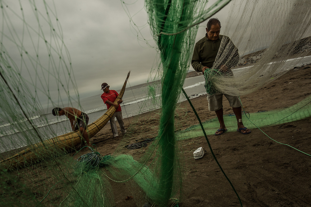 HUANCHACO, PERU - JULY 14, 2014: Carlos Ucañan Arzola, 41, (left) builds a reed boat with pointy, upswept prows known as caballitos de totora, or little totora reed horses, as Alberto Rafael Ucañan, 77, (right) mends a fishing net. Centuries before the Spanish arrived and long before the Incas extended their empire from the mountaintops to the coast, fishermen here were building boats from the totora reed that grows along the shore. Today a handful of fishermen keep up that tradition, growing and harvesting the reeds and forming them into the boats that have been used by fishermen for thousands of years in Huanchaco. PHOTO: Meridith Kohut for The New York Times