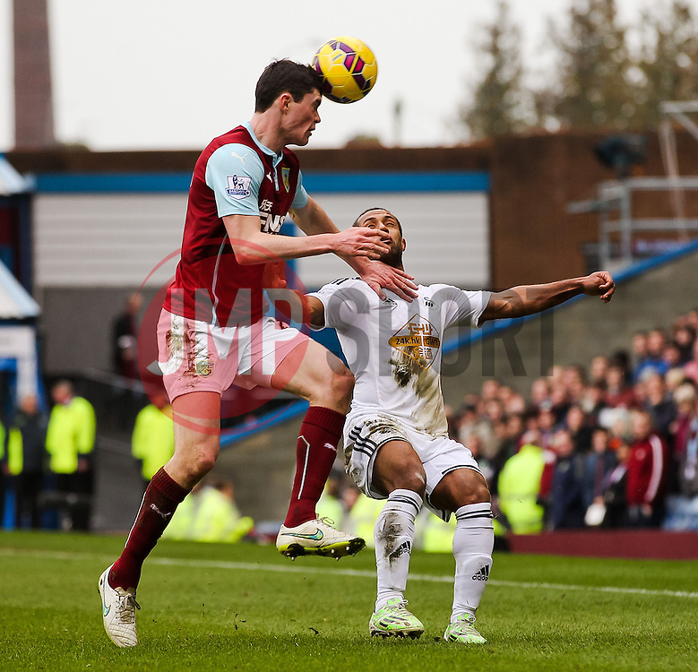Burnley's Michael Keane clears the ball ahead of Wayne Routledge of Swansea City  - Photo mandatory by-line: Matt McNulty/JMP - Mobile: 07966 386802 - 28/02/2015 - SPORT - Football - Burnley - Turf Moor - Burnley v Swansea City - Barclays Premier League