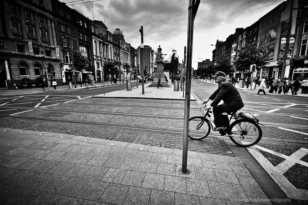 Dublin City, Ireland: A man on a Bike crosses Dublin's O'Connell Street on a Bicycle, crossing by the Luas tram Lines.